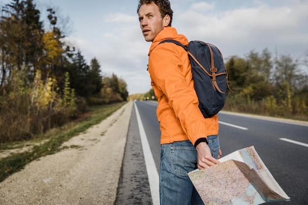 Vista lateral do homem segurando o mapa e caminhando pela estrada