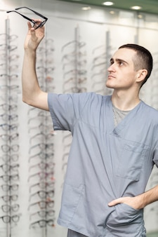 Vista lateral do homem segurando o par de óculos
