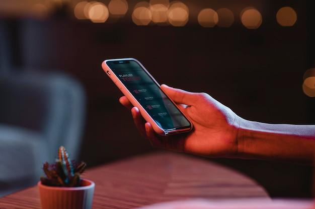 Vista lateral do homem segurando o smartphone na mão