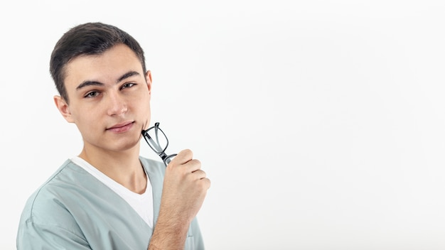 Vista lateral do homem segurando os óculos na mão, com espaço de cópia