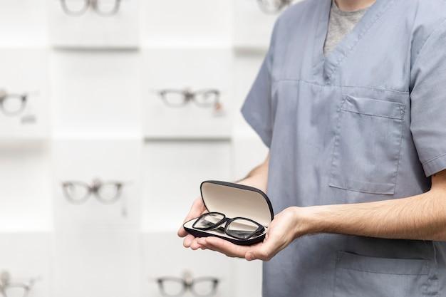 Vista lateral do homem segurando um par de óculos no caso