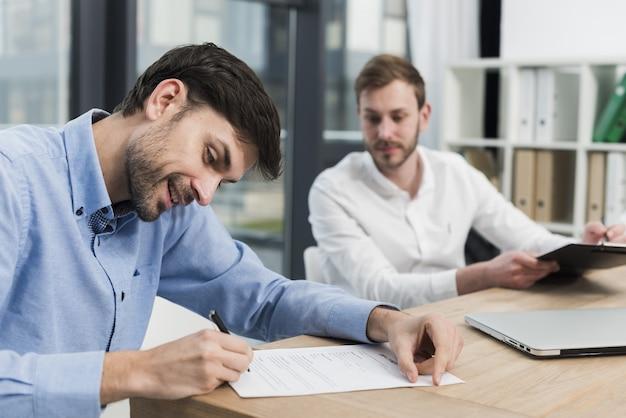 Vista lateral do homem sorridente, assinando contrato de trabalho