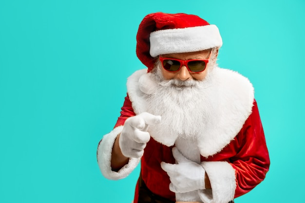 Vista lateral do homem sorridente em traje vermelho de papai noel. retrato isolado do homem sênior com barba branca em óculos de sol. conceito de férias.