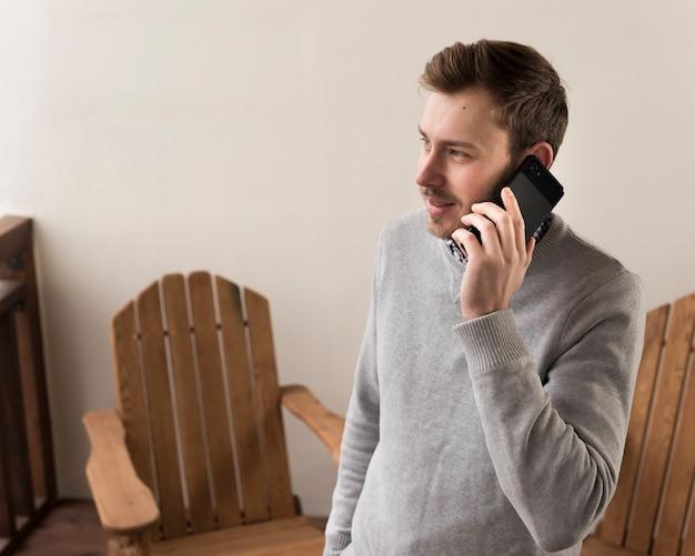 Vista lateral do homem sorridente, falando nos telefones