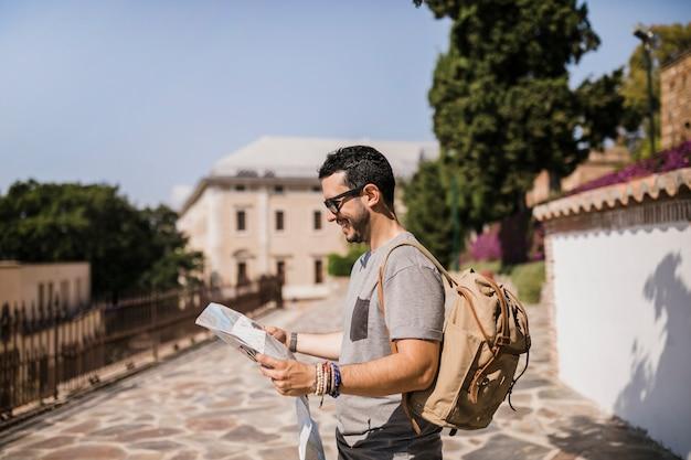Vista lateral do homem sorridente, olhando para o mapa em pé na rua