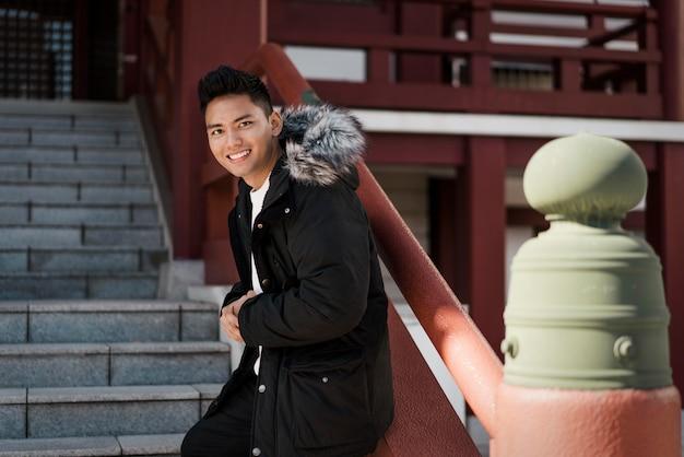 Vista lateral do homem sorridente posando na escada