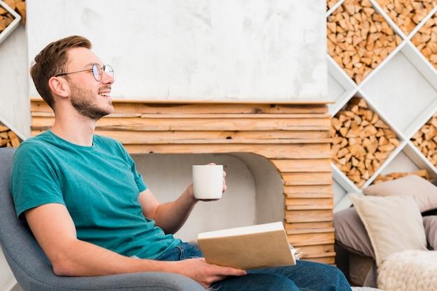 Vista lateral do homem sorridente segurando o livro com lareira