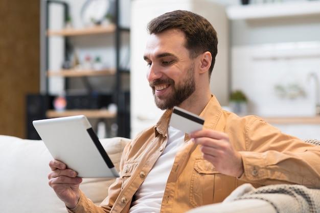 Vista lateral do homem sorridente segurando o tablet e cartão de crédito