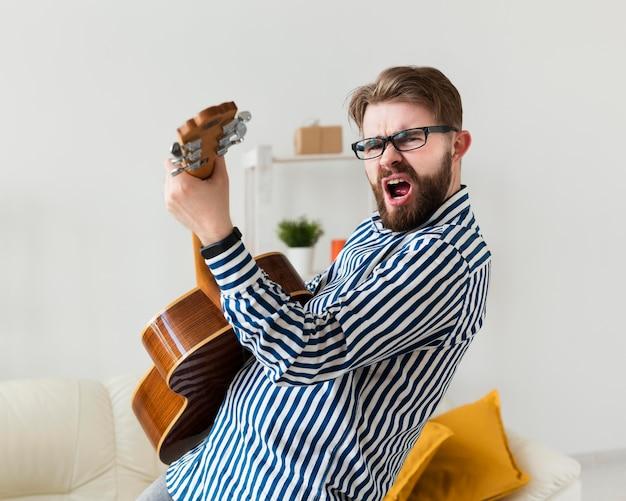 Vista lateral do homem tocando violão em casa