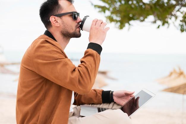 Vista lateral do homem tomando café na praia e trabalhando no laptop