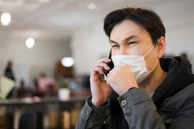 Vista lateral do homem tossindo em máscara médica enquanto fala no telefone