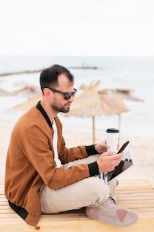 Vista lateral do homem trabalhando na praia enquanto tomando café