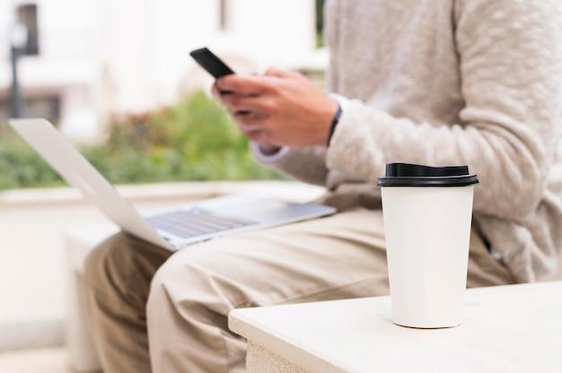 Vista lateral do homem trabalhando no laptop enquanto toma uma xícara de café