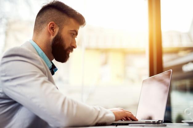 Vista lateral do homem trabalhando no laptop no escritório moderno