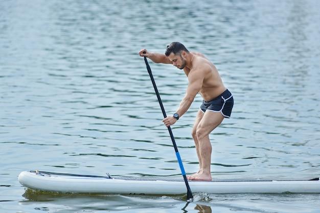 Vista lateral do homem treinando com placa sup, roaming com longa poça no lago da cidade.