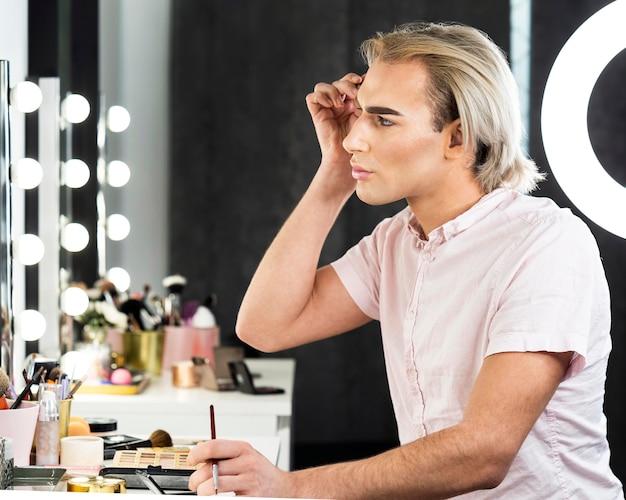 Vista lateral do homem usando maquiagem