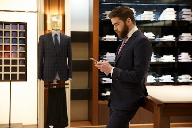 Vista lateral do homem usando smartphone