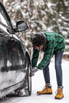 Vista lateral do homem verificando o carro