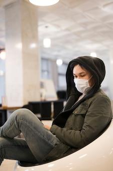 Vista lateral do homem vestindo máscara médica descansando