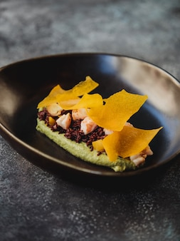 Vista lateral do húmus de espinafre verde com arroz integral e camarões em uma placa preta