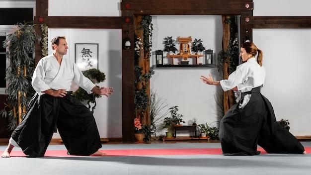Vista lateral do instrutor de artes marciais na sala de prática com o aluno