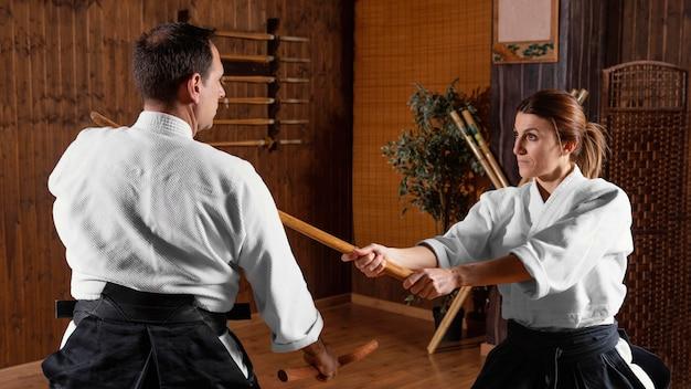 Vista lateral do instrutor de artes marciais treinando na sala de prática com a estagiária