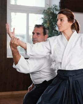 Vista lateral do instrutor de artes marciais treinando na sala de prática com o aluno