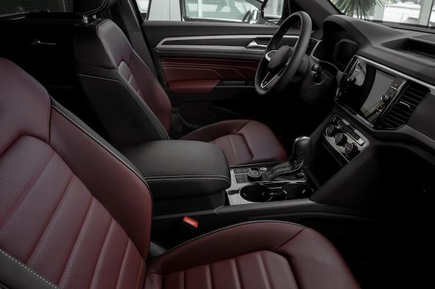 Vista lateral do interior de um carro luxuoso com bancos de couro vermelho, transmissão automática, volante e tela sensível ao toque