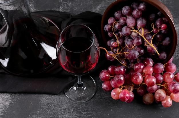Vista lateral do jarro com vinho tinto e uva no escuro horizontal