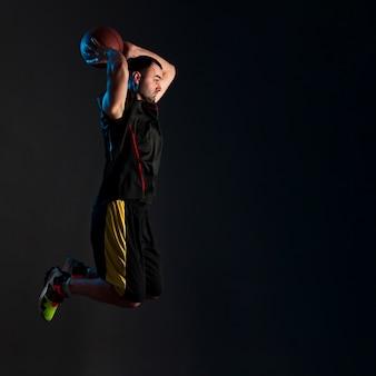 Vista lateral do jogador de basquete dunking com espaço de cópia