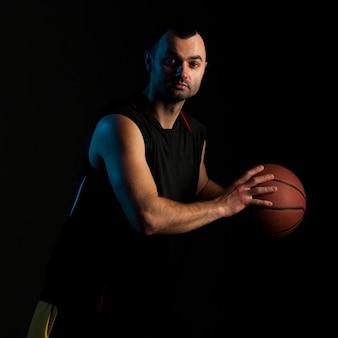 Vista lateral do jogador de basquete posando com bola