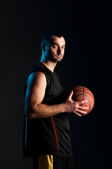 Vista lateral do jogador de basquete posando enquanto segura a bola