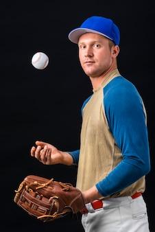 Vista lateral do jogador de beisebol brincando com bola