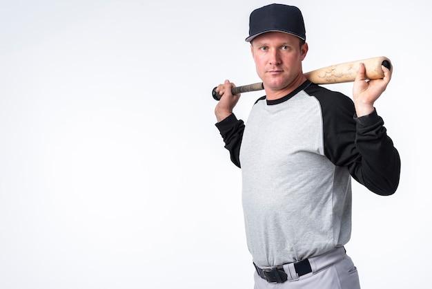 Vista lateral do jogador de beisebol com boné e taco