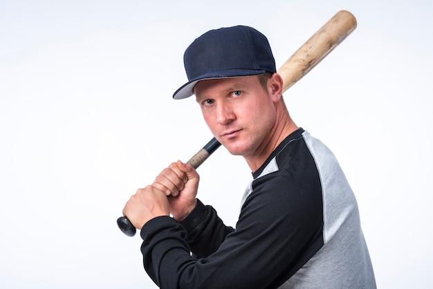 Vista lateral do jogador de beisebol segurando o bastão