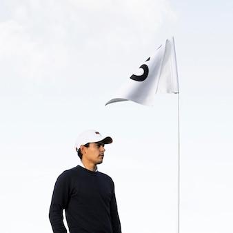 Vista lateral do jogador de golfe com bandeira