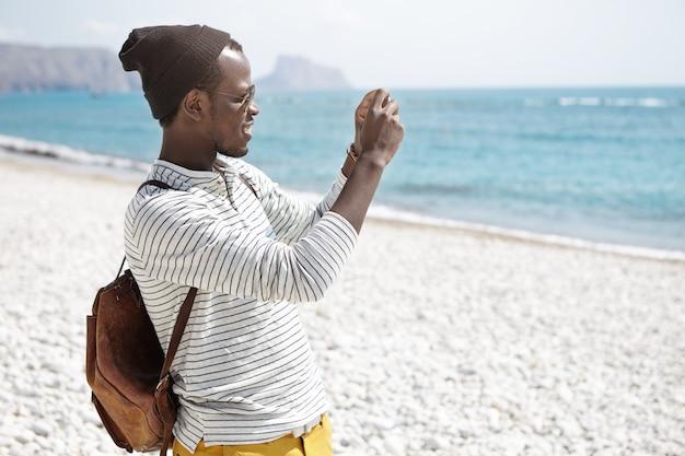 Vista lateral do jovem afro-americano com mochila, chapéu e camisa listrada, tirando fotos de pé à beira-mar na praia sozinha