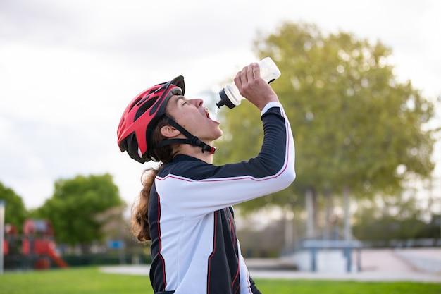Vista lateral do jovem ciclista masculina ajuste com sede no sportswear e capacete de proteção água potável no parque