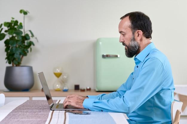 Vista lateral do jovem de camisa azul, trabalhando em casa com seu laptop. decoração simples, mas moderna, com cores suaves