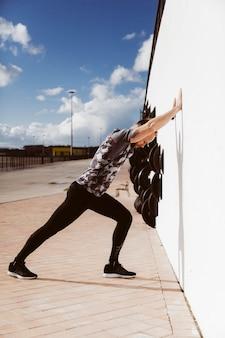 Vista lateral do jovem desportivo fazendo flexões na parede