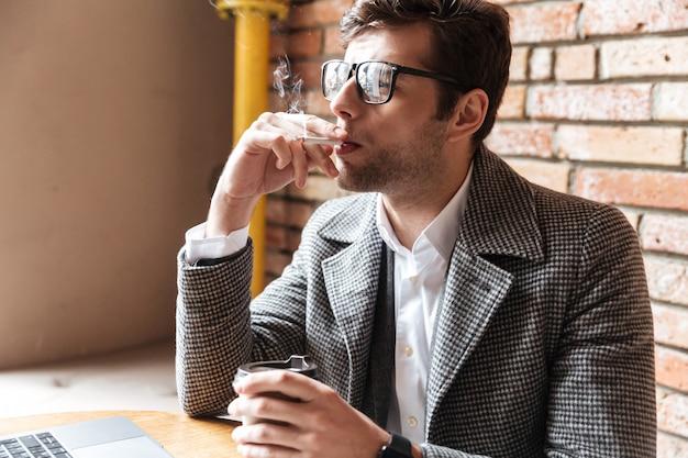Vista lateral do jovem empresário de óculos