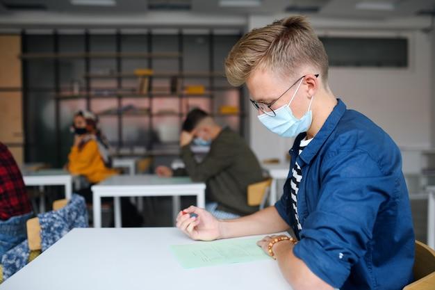Vista lateral do jovem estudante com máscaras nas carteiras na faculdade ou universidade, o conceito de coronavírus.