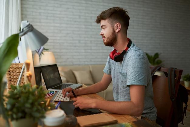 Vista lateral do jovem estudante fazendo lição de casa para a aula de design