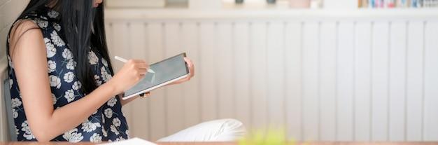 Vista lateral do jovem estudante universitário feminino escrevendo sobre tablet digital na moderna sala de estar