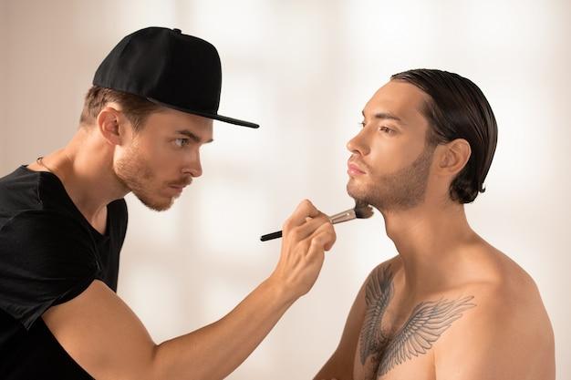 Vista lateral do jovem maquiador sério com pincel aplicando pó no queixo de modelo masculino com tatuagem no peito contra a parede branca