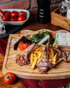 Vista lateral do kebab de costelas com batatas fritas arroz e legumes em uma placa de madeira