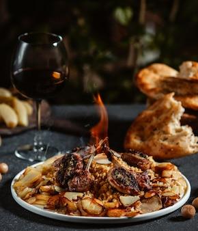 Vista lateral do kebab de costelas de cordeiro com batatas fritas em uma mesa preta
