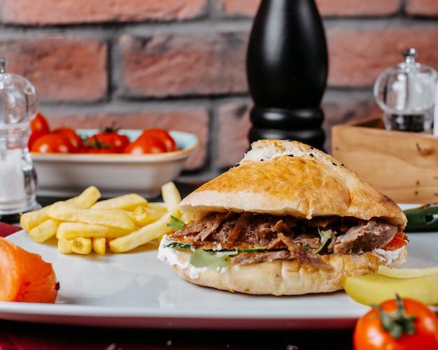 Vista lateral do kebab de doner turco com batatas fritas em um prato