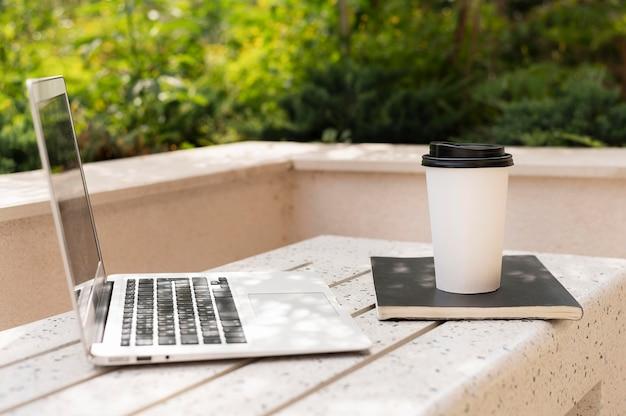 Vista lateral do laptop com uma xícara de café ao ar livre