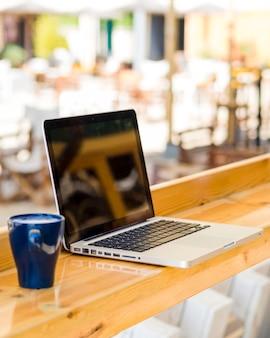 Vista lateral do laptop com uma xícara de café